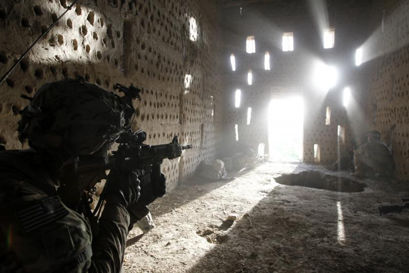 A U.S. soldier points his rifle at a doorway after coming under fire by the Taliban while on patrol in Kandahar province, Afghanistan. April 2012.