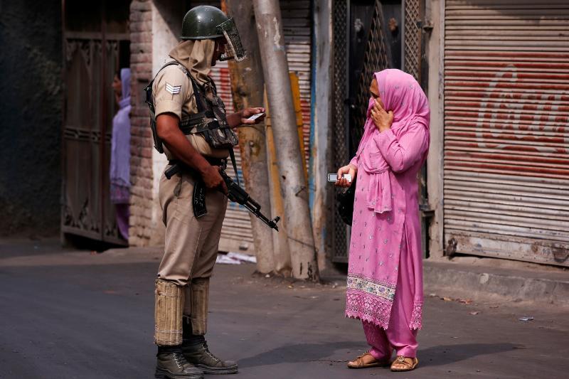 An Indian policeman checks a woman's identity card in Srinagar, July 2016.