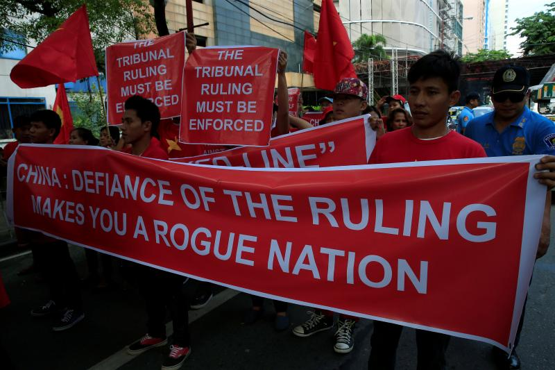 Filipino and Vietnamese activists display a banner and placards during a rally over the South China Sea disputes in front of a Chinese Consulate in Makati city, metro Manila, Philippines August 6, 2016.