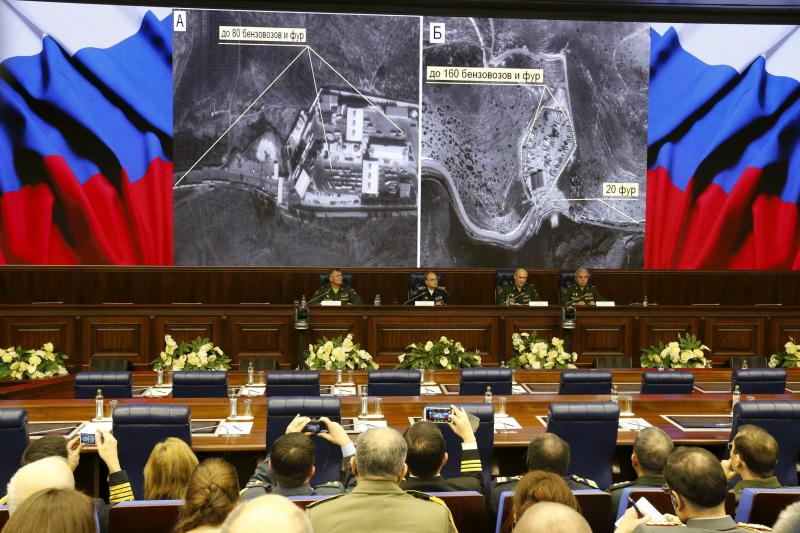 Defense ministry officials sit under screens with satellite images on display during a briefing in Moscow, Russia, December 2, 2015. Russia's defense ministry said on Wednesday it had proof that Turkish President Tayyip Erdogan and his family were benefit