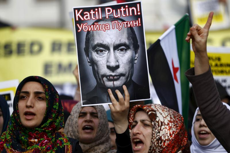 """Pro-Islamist demonstrators, holding a defaced poster of Russia's President Vladimir Putin, shout slogans during an anti-Russian protest in Istanbul, Turkey November 27, 2015. A slogan in Turkish and Russian on the poster reads as """"Killer Putin!"""""""