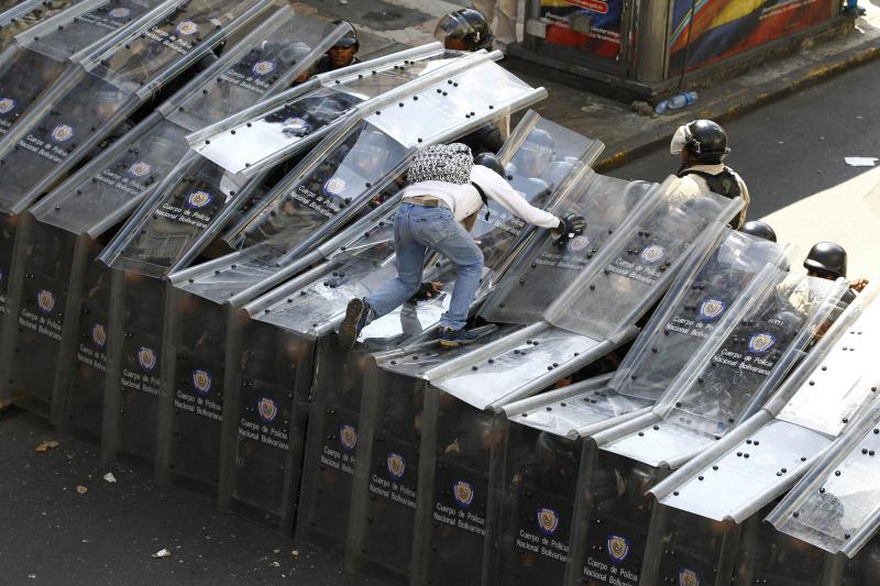 A protestor clashes with riot police in Caracas, February 2014.