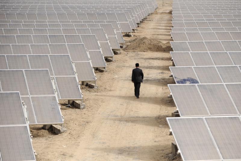 A man walks between constructed solar panels under construction in Xinjiang, April 2012.