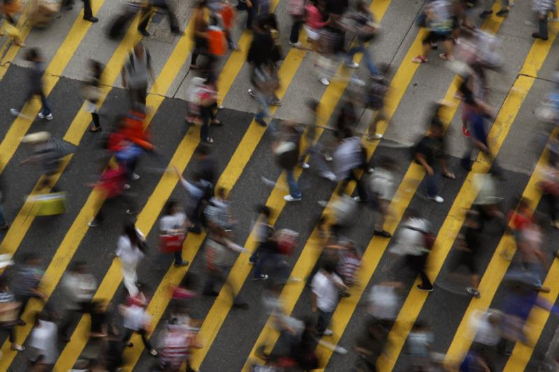 People cross a street in Mong Kok district in Hong Kong, October 4, 2011. Mong Kok has the highest population density in the world, with 130,000 in one square kilometer.