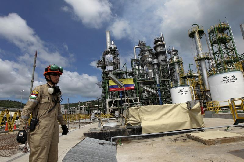 Oil workers are seen in front of a refurbished oil refinery in Esmeraldas, Ecuador December 17, 2015.