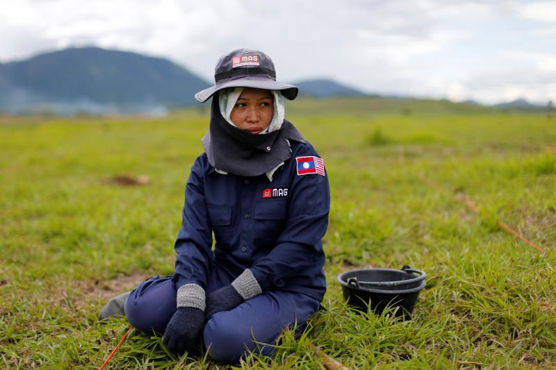 A technician from the NGO Mines Advisory Group (MAG) pauses in a field while searching for unexploded bombs that were dropped by the U.S. Air Force planes during the Vietnam War in Xieng Khouang province, Laos September 2, 2016.