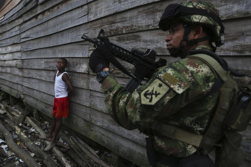 """A Colombian Special Forces soldier patrols a street in the """"La Playita"""" neighborhood, during a visit by Defence Minister Juan Carlos Pinzon in the port city of Buenaventura March 21, 2014."""