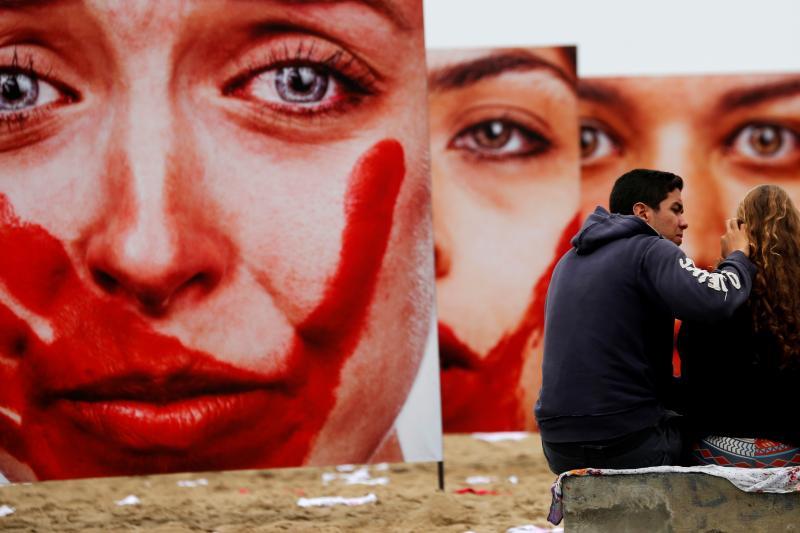 Activists talk in front photos from Brazilian photographer Marcio Freitas, during a protest by non-governmental organization (NGO) Rio de Paz (Rio of Peace) against rape and violence against women on Copacabana beach in Rio de Janeiro, Brazil, June 6, 201