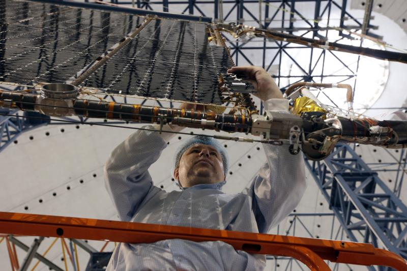 """Sergei Mareev, electricity specialist of the """"Kvant"""" (Quantum) research-and-production enterprise, works on a solar battery for the Express AM6 new generation geostationary telecommunications heavy satellite in the Siberian town of Zheleznogorsk, April 2,"""