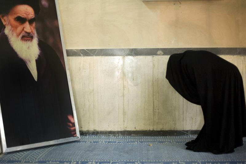 A woman kneels before a portrait of the Ayatollah Khomeini, June 2007.
