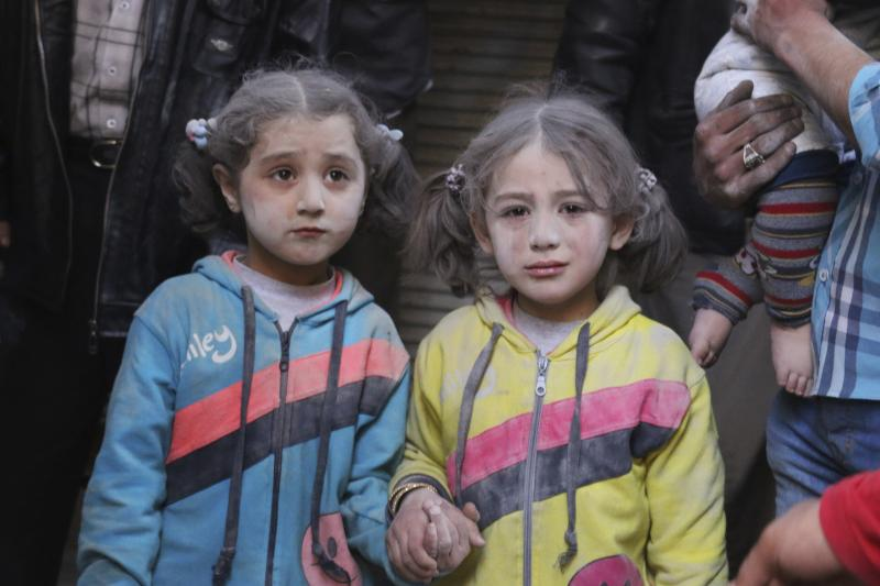 Girls who survived what activists said was a ground-to-ground missile attack by forces of Syria's President Bashar al-Assad, hold hands at Aleppo's Bab al-Hadeed district April 7, 2015.