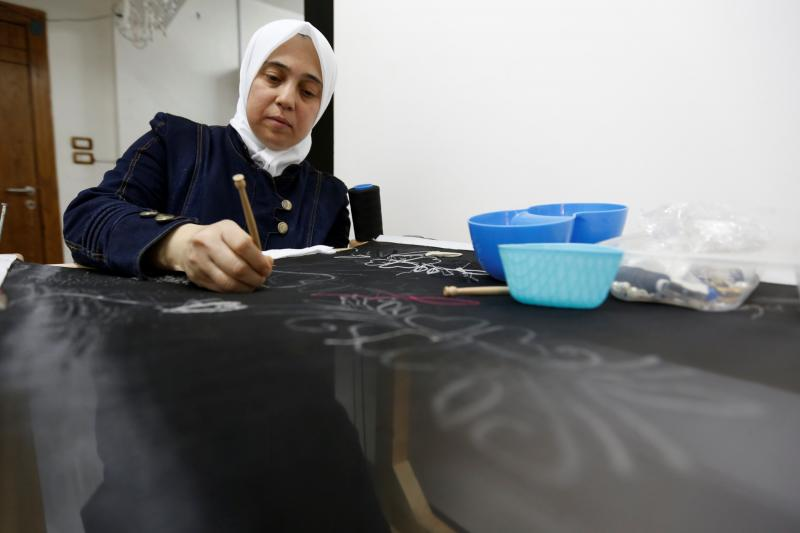 Rana, a Syrian refugee, works on a handmade loom under Jasmine, a project which hires and trains Syrian refugee women to create handicrafts, in Amman, Jordan, July 11, 2016.