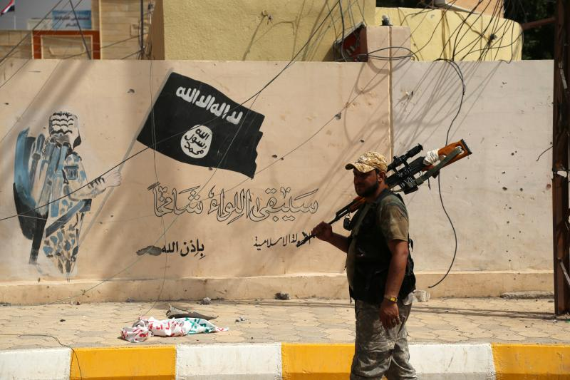 A member of the Iraqi security forces walks past a wall painted with the black flag commonly used by Islamic State militants in Shirqat, Iraq, September 22, 2016.
