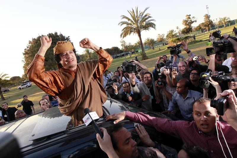 Libyan leader Muammar Gaddafi waves from a car in the compound of Bab Al Azizia in Tripoli, after a meeting with a delegation of five African leaders seeking to mediate in Libya's conflict April 10, 2011.