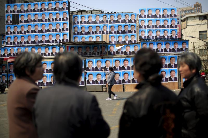 People look at a building covered in hundreds of posters of Chinese President Xi Jinping in Shanghai, China, March 26, 2016.