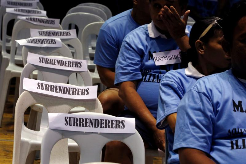 Alleged drug users take a pledge not to use meth after surrendering to Philippine police.