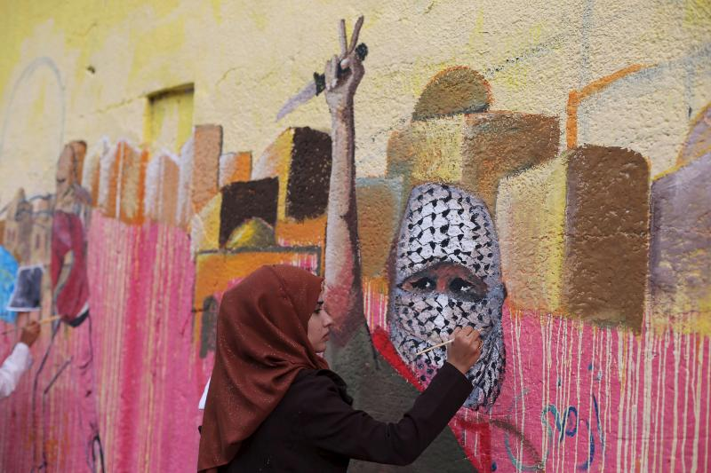 A Palestinian woman paints a mural, depicting a masked Palestinian holding a knife, in support of Palestinians committing stabbing attacks against Israelis, in Rafah in the southern Gaza Strip November 3, 2015.