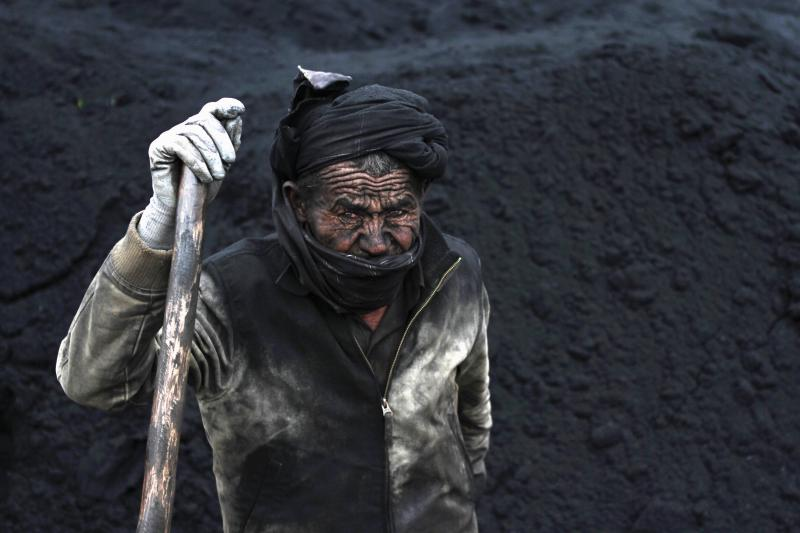 A labourer takes a break at a coal dump site outside Mazar-i-Sharif, November 6, 2014.