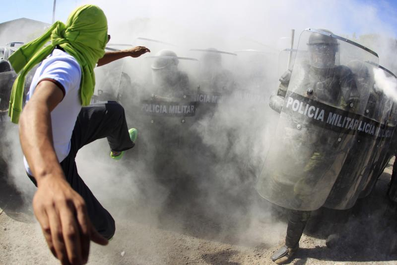 An activist clashes with police at a demonstration in Guerrero, Mexico, January 2015.