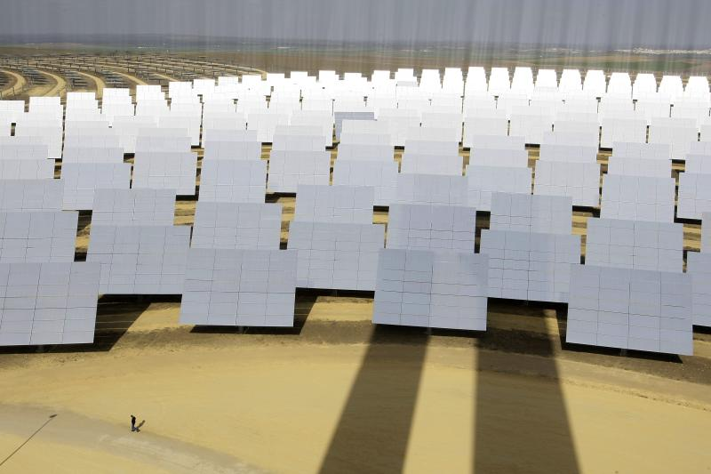 A man walks next to solar panels at a soon-to-be completed solucar solar park at Sanlucar La Mayor, near Seville, February 13, 2008.