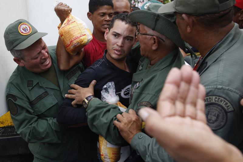 Soldiers and shoppers argue at a state-run market in Caracas, January 2015.