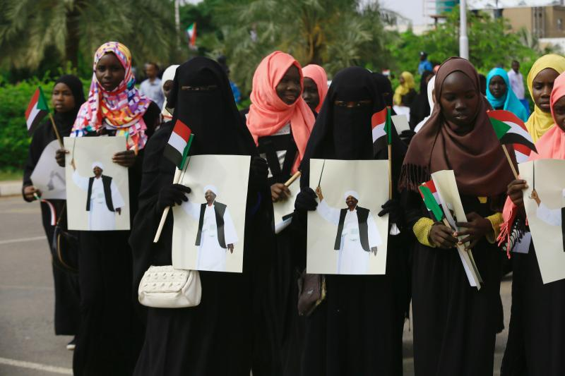 Supporters carry images of Sudan's President Omar al-Bashir during a rally against the International Criminal Court (ICC), at Khartoum Airport in Sudan, July 30, 2016.