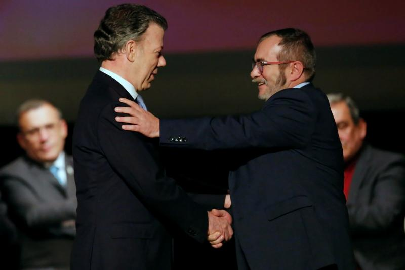 Colombian President Juan Manuel Santos and FARC leader Rodrigo Londono, known as Timochenko, shake hands after signing the peace accord in Bogota, Colombia November 2016.