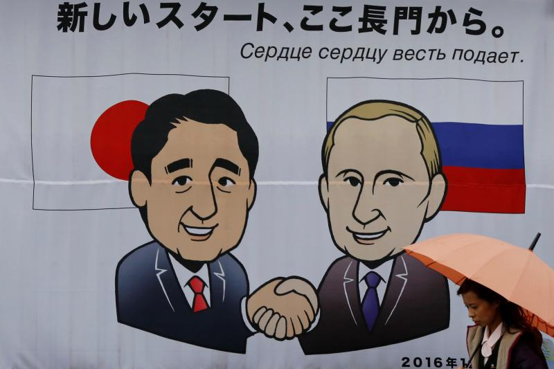 """A woman walks past a banner showing Japan's Prime Minister Shinzo Abe and Russian President Vladimir Putin at the Senzaki station in Nagato, Yamaguchi prefecture, Japan, December 14, 2016, a day before their summit meeting. The words on top reads, """"A new"""