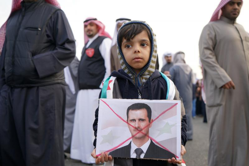 A boy holds a crossed out image of Syria's President Bashar al-Assad during a protest across the street from the Russian Embassy in Shaab, Kuwait, December 2016.