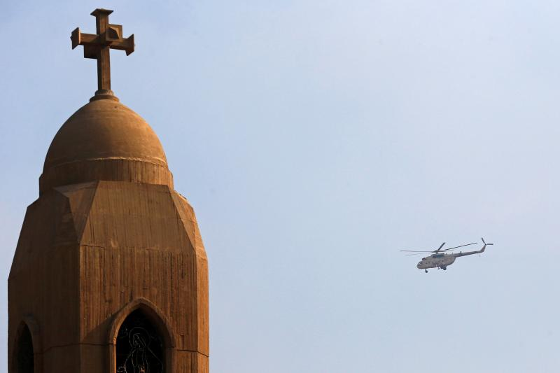 A military helicopter flies above the Virgin Mary church during the funeral for victims killed in the bombing of Cairo's main Coptic cathedral, in Cairo, Egypt, December 2016.