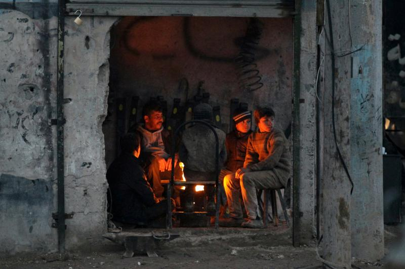 People sit around a fire in the rebel-held Syrian town of al-Rai, January 2017.