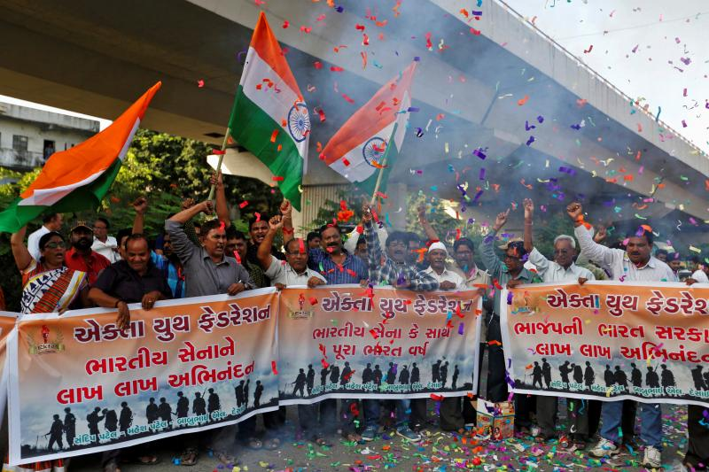 People wave national flags to celebrate after India said it had conducted targeted strikes across the de facto frontier, in Ahmedabad, India, September 2016.