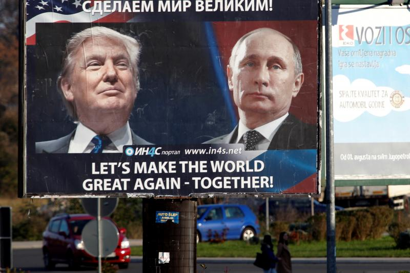 Pedestrians cross the street behind a billboard showing pictures of Trump and Putin in Danilovgrad, Montenegro, November 16 2016.