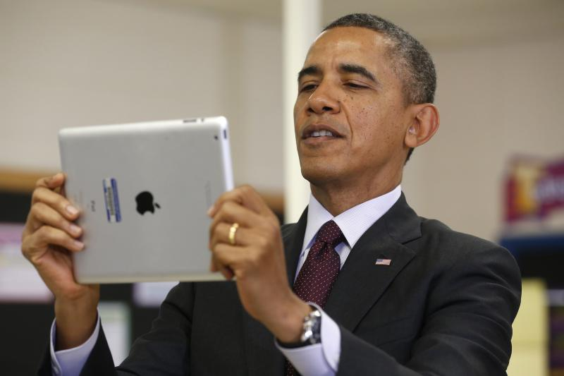 U.S. President Barack Obama holds an iPad during a visit to a high school in Adelphi, Maryland, February 2014.