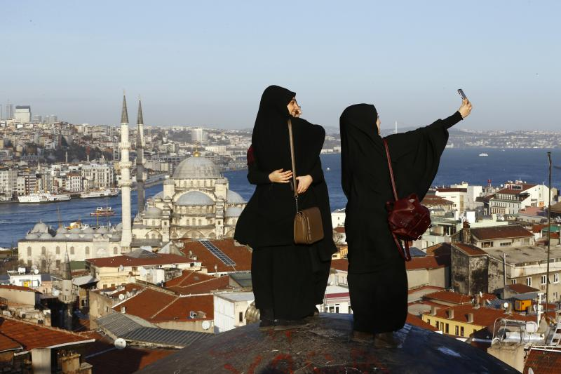 Young women take selfie photographs in front of the New Mosque by the Bosphorus strait in Istanbul, Turkey January 12, 2016.