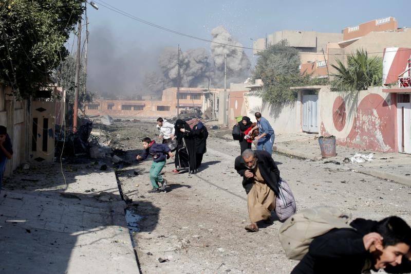 People run after a coalition airstrike hits the Tahrir neighborhood of Mosul, Iraq, November 2016.