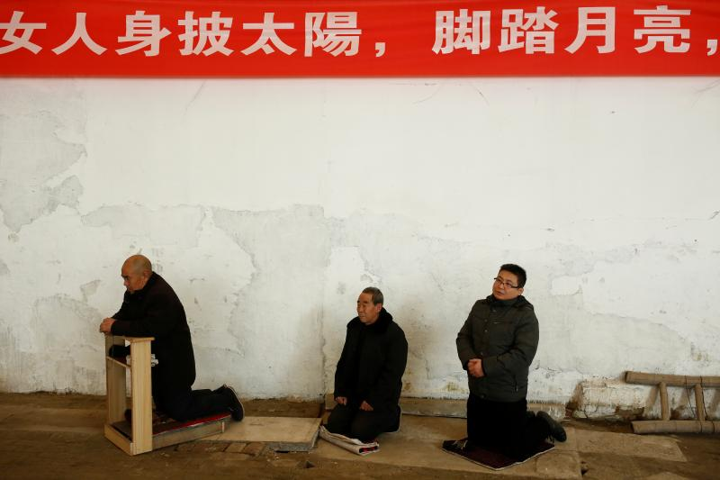 Men attend Sunday service at a makeshift, tin-roofed church in Youtong village, China, December 2016.