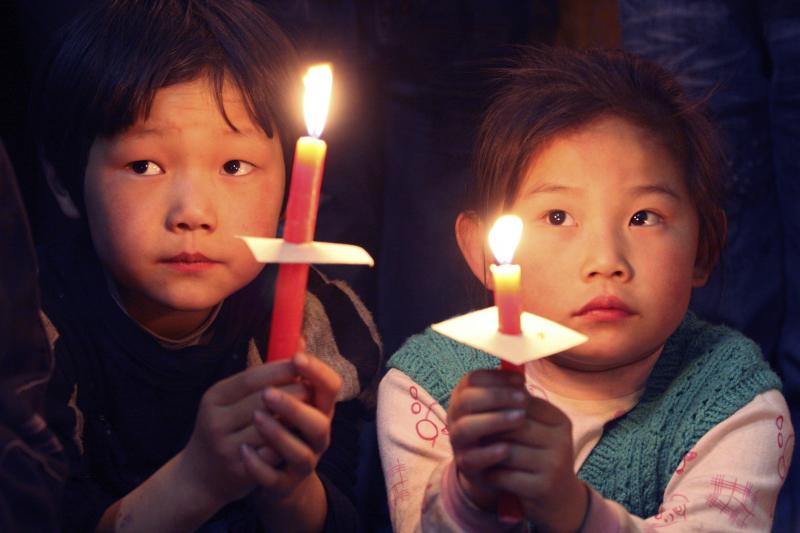 Children hold candles during the Easter mass at a church in Xiaohan, China, April 2009.