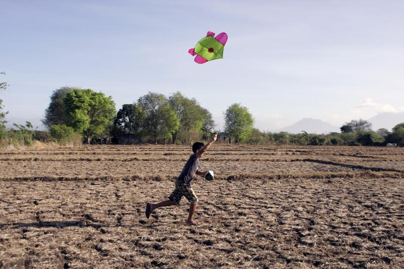 A boy flies his kite on dry and cracked farmland in San Juan town, Batangas province, south of Manila, April 18, 2010.