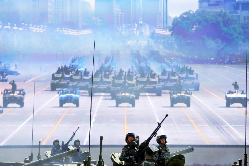 Chinese soldiers drive their armoured vehicles to Tiananmen Square as others are shown on a screen during the military parade marking the 70th anniversary of the end of World War II, in Beijing, China, September 2015.