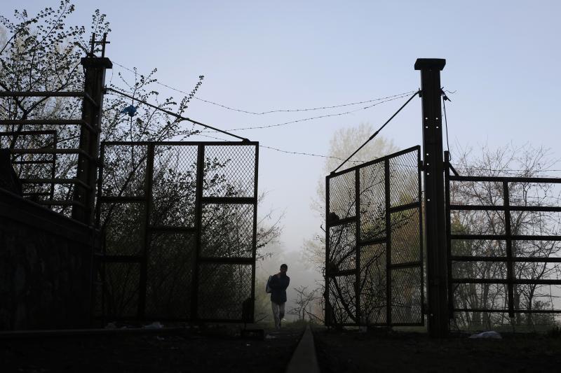 A refugee walks through a gate at a refugee camp near Idomeni, Greece, March 2016.