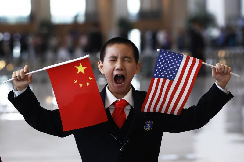 A Chinese boy waits to greet U.S. Secretary of State Hillary Clinton at the National Museum in Beijing, May 2012.