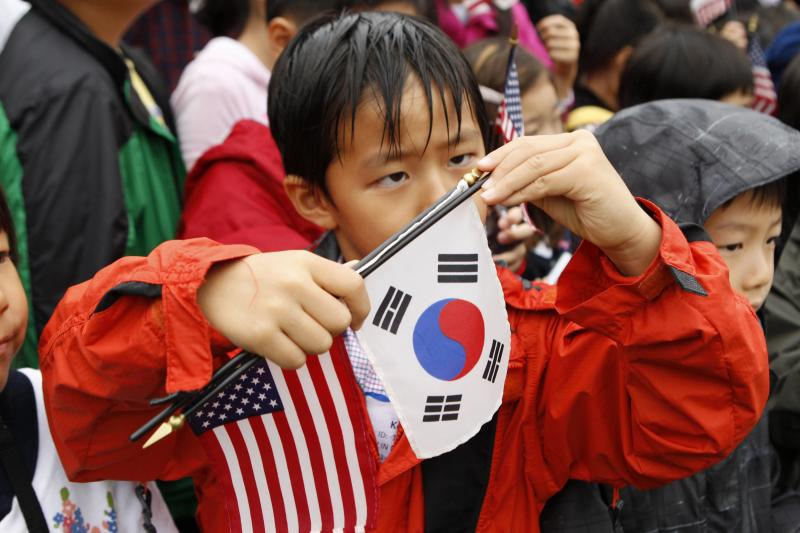 A child adjusts a South Korean flag as he awaits the  arrival of South Korean President Lee Myung-bak at the White House in Washington, October 2011.
