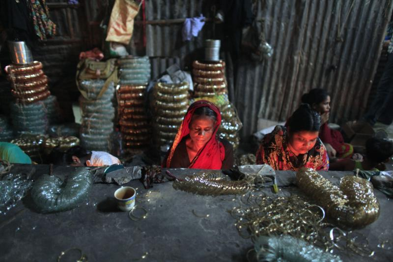 Labourers work in front of small kilns at a glass bangle factory in Old Dhaka, July 2012.