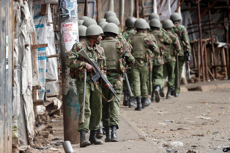 Kenyan policemen walk during clashes with supporters of opposition leader Raila Odinga, in Kibera slum, in Nairobi, Kenya, August 2017.