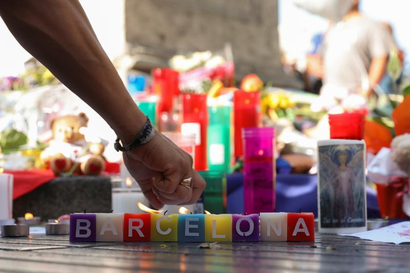 A man lights a candle in an impromptu memorial a day after terrorist attack at Las Ramblas in Barcelona, Spain, August 18, 2017.