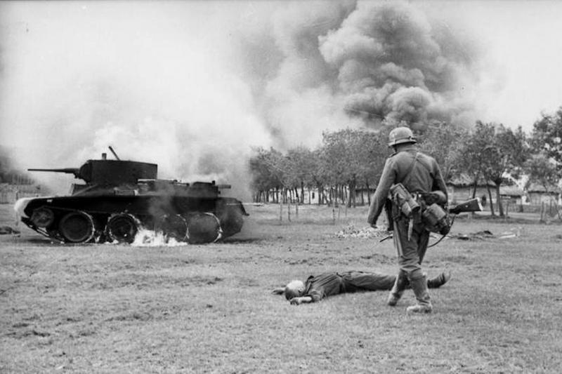 A Germant infantryman walks toward the body of a Soviet soldier and burning Soviet BT-7 tank in the early days of Operation Barbarossa, 1941