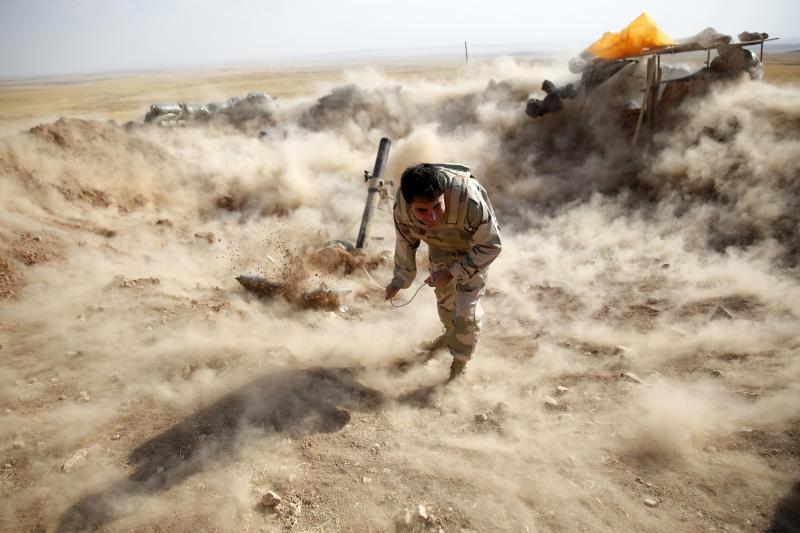A Kurdish fighter launching mortar shells toward ISIS-held territorty near Mosul, Iraq, September 2014.