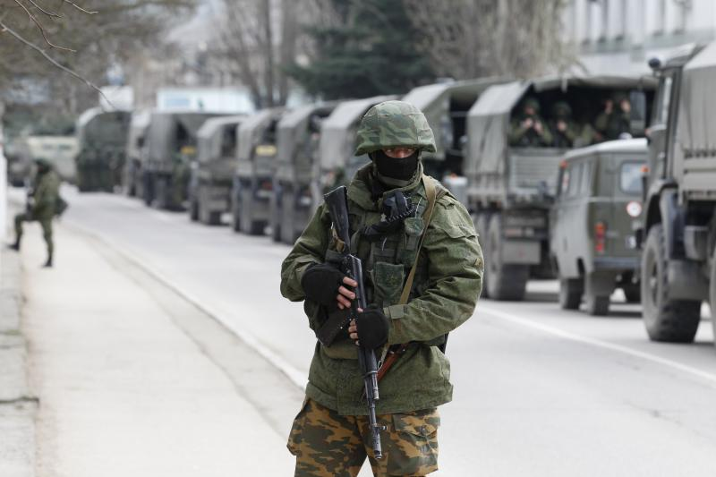 Armed servicemen wait in Russian army vehicles outside a Ukrainian border guard post in the Crimean town of Balaclava, March 2014