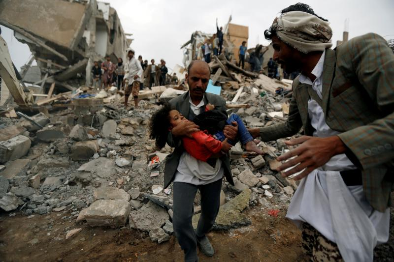 A man carries an injured girl, rescued from the site of a Saudi-led air strike in Sanaa, Yemen, August 2017